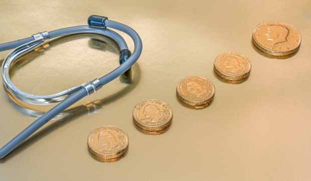 Stethoscope and gold coins on a golden background