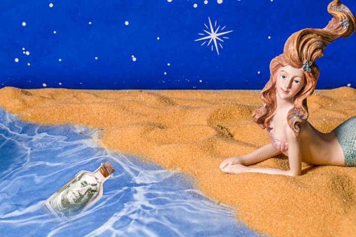 Lucky mermaid finds a bottle with cash floating on the water.